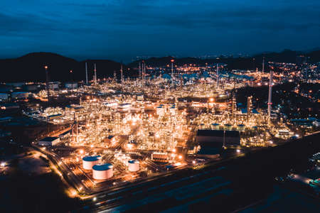 Aerial view of petroleum oil refinery in industrial estate at twilight. Fuel and power generation, petrochemical factory industry, or environmental pollution concept