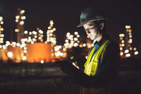 Asian man engineer using digital tablet working late night shift at petroleum oil refinery in industrial estate. Chemical engineering, fuel and power generation, petrochemical factory industry concept Stock fotó