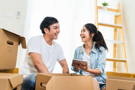 Happy young Asian couple moving in to new house, using digital tablet organizing things and unpacking boxes together. Home relocation, domestic lifestyle, or love relationship concept