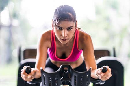 Hermosa mujer asiática haciendo ejercicio en la máquina de ciclismo estacionaria en el gimnasio interior, cara de determinación. Actividad recreativa deportiva, entrenamiento de personas o concepto de estilo de vida saludable