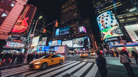 New York City, United States - Apr 4, 2019: Crowded people, car traffic transportation, billboards and advertising signs at night in Times Square. American lifestyle or modern city life concept Sajtókép