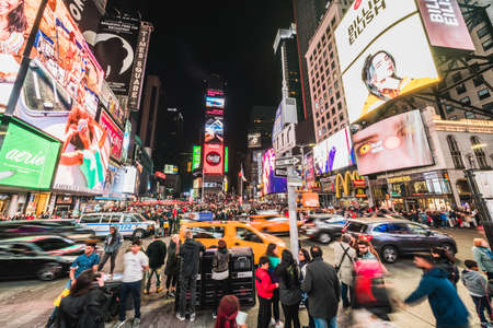 New York City, United States - Mar 31, 2019: Crowded people, car traffic transportation and billboards displaying advertisement at night in Times Square. American lifestyle or modern city life concept Sajtókép