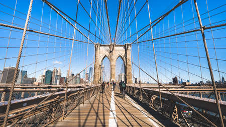Unidentified people walk and ride bicycle on Brooklyn bridge in New York City, sunny day. United states tourism landmark, American city life, USA tourist attraction, or commuter transportation concept Stock fotó