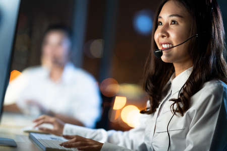 Asian woman work as customer support service or call center phone operator, using desktop computer and microphone headset, late night shift. Overtime office life, telemarketing or sales job concept