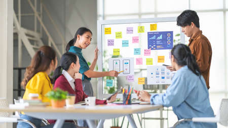 Young Asian woman leading business creative team in mobile application software design project. Brainstorm meeting, work together, internet technology, girl power, office coworker teamwork concept Stock fotó