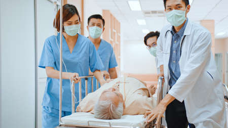 Group of Asian emergency doctor and nurse team wear face mask, push emergency stretcher, transport senior patient in hospital. Health care paramedic service, or medical rescue team operation concept