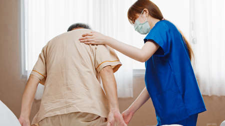 Female Asian nurse support senior male patient stand up and walk from bed in hospital. Nursing home, medical service, physiotherapy, hospitality, or recovery treatment concept