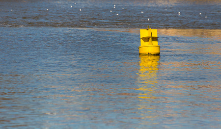 Yellow iron buoy floats in the blue water the river shows the level of the ships to the ships for a safe walk Imagens
