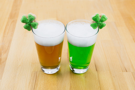 Two glasses of beer one green with white foam with clover on a wooden table to celebrate the day of St. Patrick