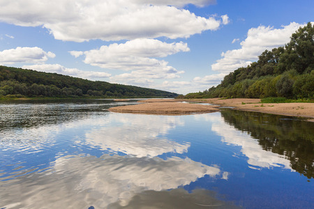 Sand island among the calm surface of the river along the banks of the forest rest relaxation in a sunny day Stock Photo