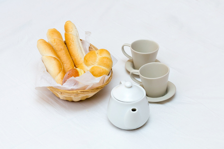 Two cups on saucers teapot wicker straw basket with bread light breakfast snack on white background Stock Photo