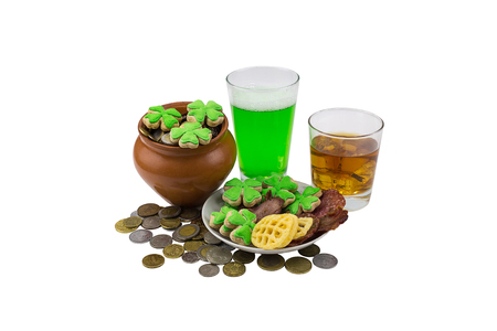 Scotch whiskey on the rocks with a green beer with snack plate of clover and a clay pot with coins. Patrick saint day