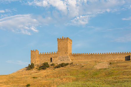 Krym Sudak ruins of an old fortress on a green hill, with a piece of gear stone walls. Genoese fortress Stock Photo