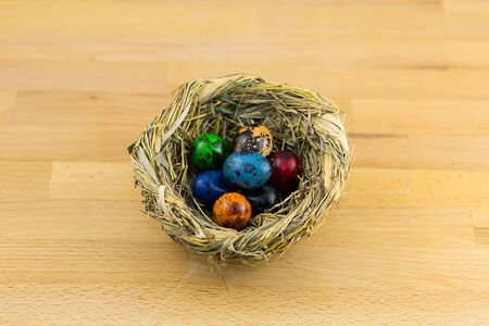 wicker nest of straw colored eggs are blue green red tone
