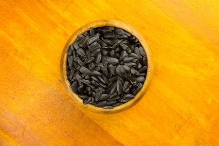 sunflower seeds: Sunflower seeds close-up in wooden bowl beautiful light bite delicious useful Stock Photo