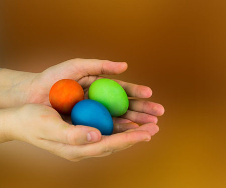 Three eggs lie in the palms of hands red green blue on a brown blurred background