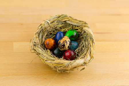 straw nest with colored eggs in small quail standing on a wooden table