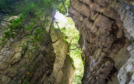 hidden white rocky gorge in the view of the valley below with a narrow rock corridor meshed walls Stock Photo