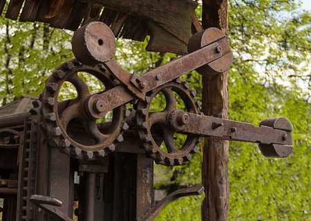 antique factory: Minsk Belarus Republic- industrial background rusty old large toothed gear mechanism processing timber located on the street may 2016