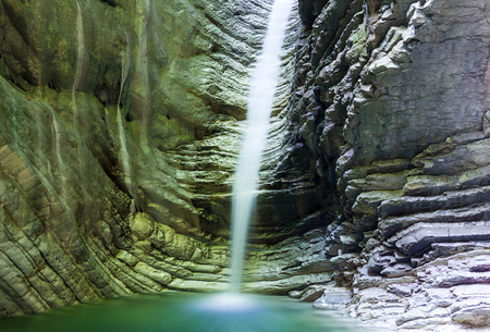 Waterfall in a rock with shiny water lit by sunlight water as a mist flows into a blue natural pool