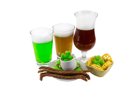 clovers: three glasses of beer bamboo unfiltered stout with a variety of snacks and biscuit clover with green mastic. Celebrating St. Patricks Day
