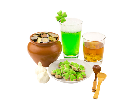 gratuity: Patricks Day celebrations glass of whiskey scotch with three slices of ice a glass of green beer with garlic for a snack and a biscuit paying a bill of peas with coins