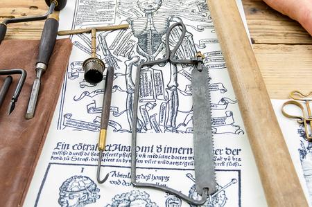 medical doctors: Old medical instruments surgical saw hook on background engraving human skeleton