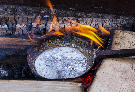 Vessel frying pan with molten metal aluminum lead preparation for casting against the background of an orange flame
