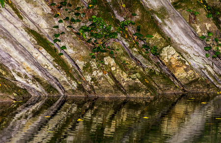 Monolithic wall of rock covered with moss and ivy reflected in the water of the lake river Stock Photo