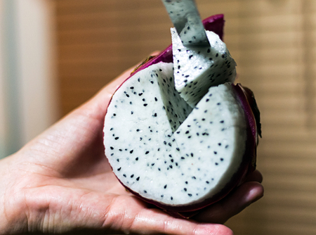 juicy dragon fruit lying in the hand slicing fruit triangular piece close-up