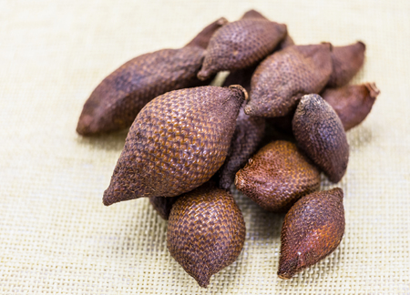 handful of snake fruit close-up on a light wicker background. Scaled sweet fruit of Asia