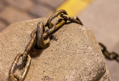 cement curbstone metal hook with chain rustic links on blurred background cobbled urban background Stock Photo
