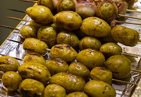 lumpy potatoes baked with the skin on a wooden skewer, lies on padonne covered with foil close-up Stock Photo
