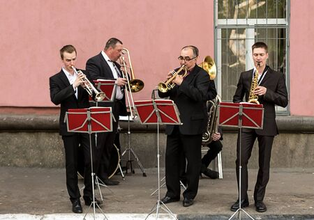 wind street ensemble saxophone trumpet, a city day celebration. Four musicians in classic black suits play on wind instruments. Tver July 2017 에디토리얼