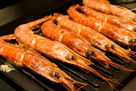 large shrimp whole langoustines bbq on the background of an iron grill grate 스톡 콘텐츠