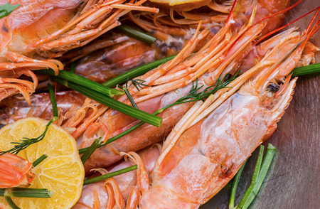 many whole langoustine with head and claws slice of lemon with dill branches