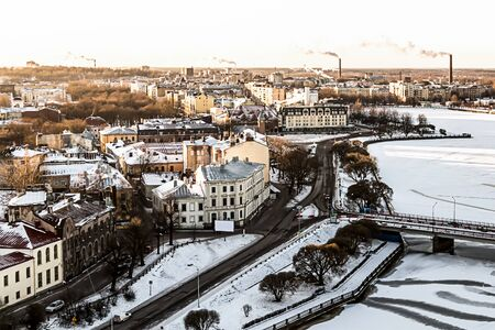 panoramic view of the snow-covered city  Vyborg  of choice facades of houses on the background of industrial steam from the pipes road a river-ice covered river and bridge, Vyborg Russia January 2017