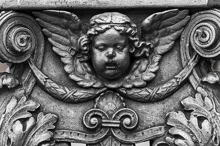 bronze decor elements decorating the sculpture of the head of Cupid angel with figured wings of monograms with a vegetable pattern covered with silver paint. Czech Republic Prague March 2017