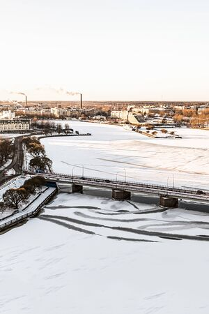 bridge stone industrial automobile modern through a frozen river covered with ice snow against the background of the city panorama of Vyborg. Vyborg, Russia, January 2017 에디토리얼