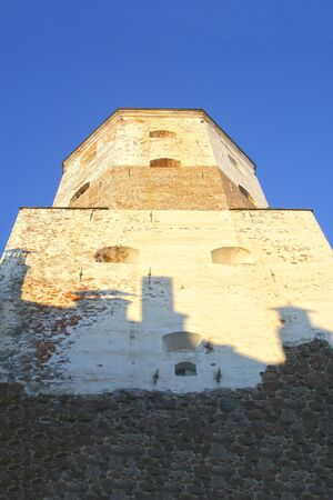 tower saint Olaf on a blue sky close-up white brick bottom edge of an old stone powerful defense on a castle island. Vyborg Russia January 2017