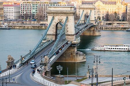 suspension chain bridge connects the two banks of Pest and the pedestrian pedestrian boulevards decorated with stone lions over the wide river Danube. Budapest Hungary February 2018