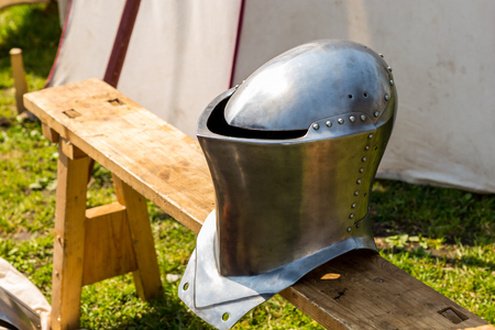 helmet iron shining medieval warrior defense army forged rivets on the background of a marching tent