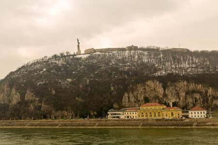 statue of liberty high on the hill gellert against a cloudy sky over the snow-covered bank of the Danube. Hungary Budapest March 2018