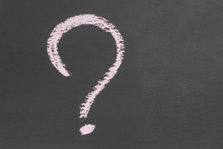 Question mark Icon drawn in chalk on a dark slate Copy space design background Stockfoto