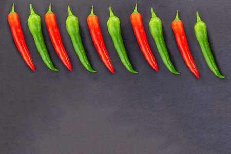 base of red green pods of hot pepper border top frame on black background design copy space Banco de Imagens