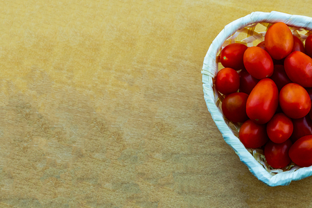 culinary design a bunch of cherry tomatoes mini vegetables in a white basket on a wooden background copy space 写真素材