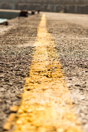 marking separating yellow stripe road, label extending far close-up. Perspective vertical photo yellow strip road