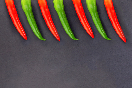design base long pods of hot pepper vegetable part bright red green border on black substrate