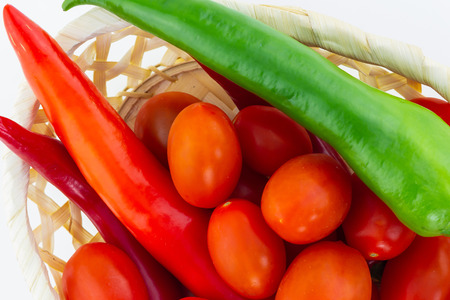 long peppers peppers green red mini cherry tomatoes closeup wicker basket background Stock Photo