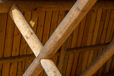 crossed thick beige crossbeams boards roof high sunlight background construction design